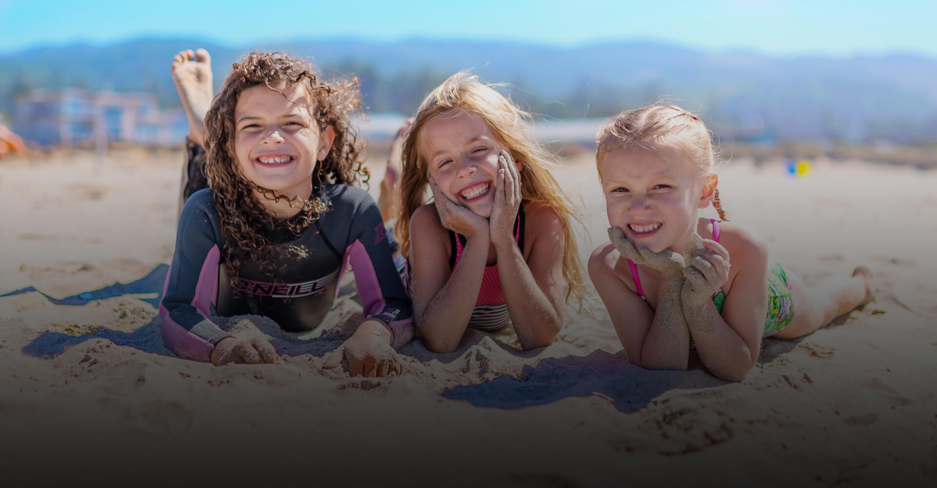 Smiling children on the beach who are the children of our Washington dentists at Smile Surfers