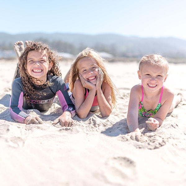 Smiling little girls laying on the beach enjoying the sun after Pediatric Dentistry