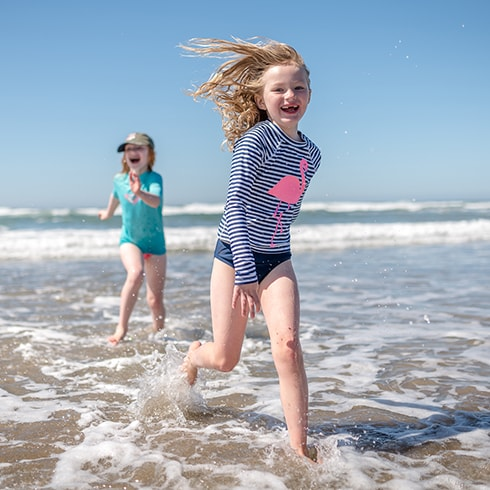 Two little girls running through the ocean with healthy smiles thanks to Pediatric Dentistry in Richland and Sumner, WA