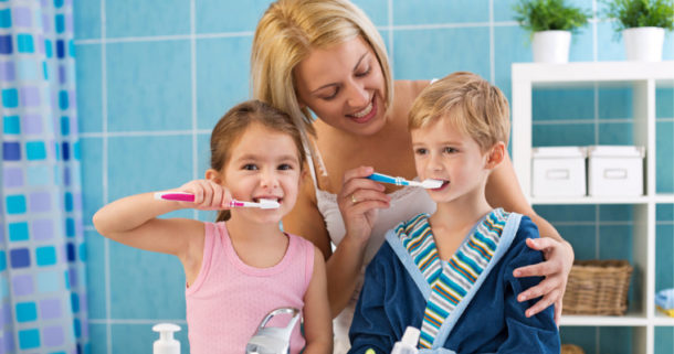 Mother helping her young son and daughter brush their teeth