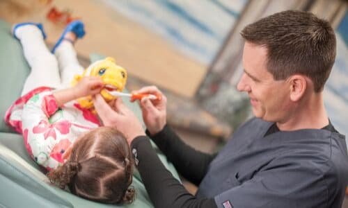 One of our pediatric dentists showing a young girl how to brush properly with a stuffed animal