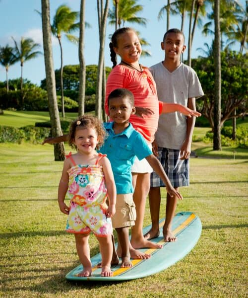 Four kids standing on a surf board smiling with palm trees in the background