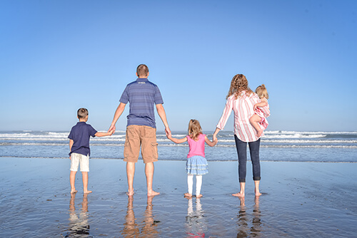 Two parents holding hands with their children on the beach